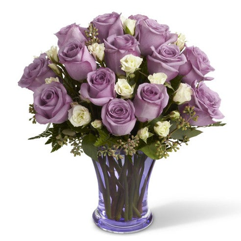 Cute valentine's day gift of purple roses in a clear glass vase