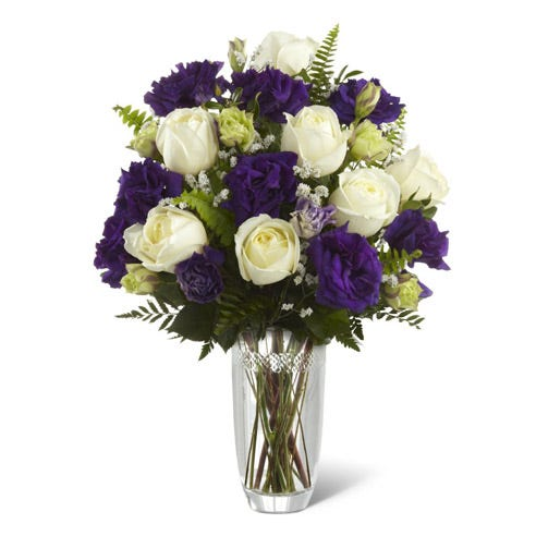 White roses and purple double lisianthus bouquet in a clear glass vase flower delivery