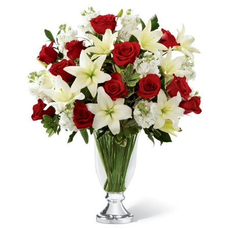 Stunning red roses and white lilies delivered in a beautiful glass vase for the holidays