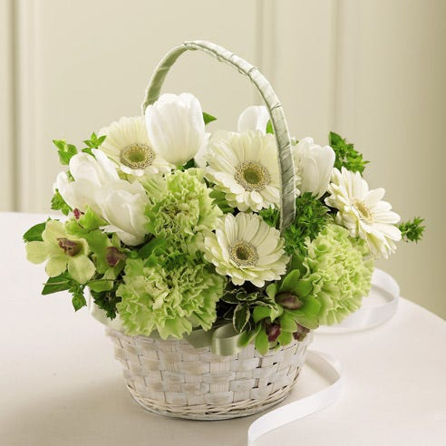 A white flower girl basket with white tulips