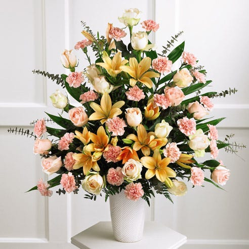 Sympathy alter arrangement with peach roses, pink carnations and lilies