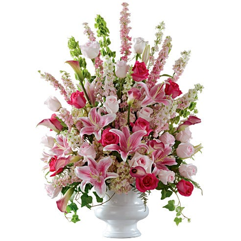 Sympathy flower arrangement with pink roses, bells of ireland and hydrangea