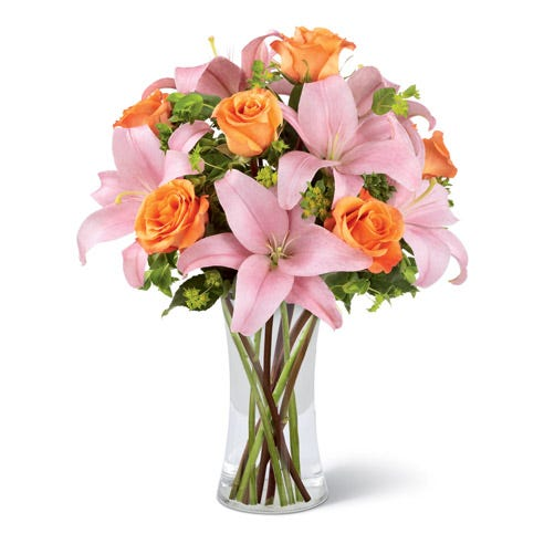 Orange roses and pink asiatic lilies with greens in a clear glass vase