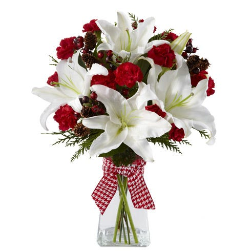 Winter flowers with white lilies and red carnations in glass vase.