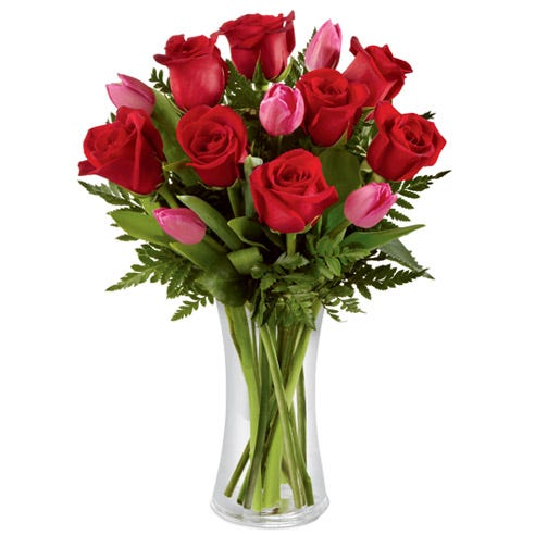 Love flowers bouquet with red roses and pink tulips in clear glass vase