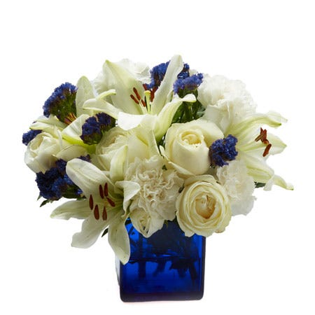 white rose and lily bouquet with flowers for men inside a blue vase