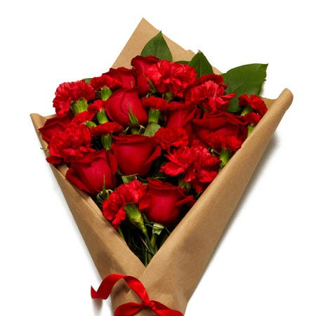 Red roses and carnations parchment paper wrapped flower bouquet