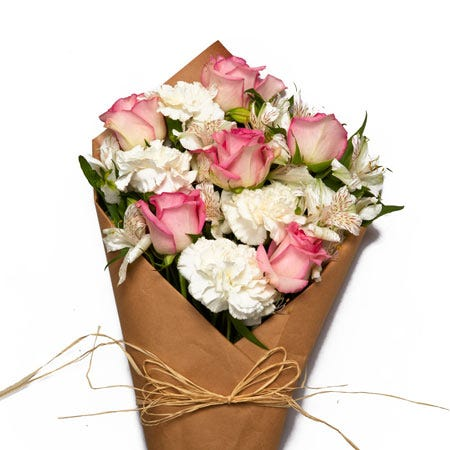 Paper wrapped pink roses and white carnations