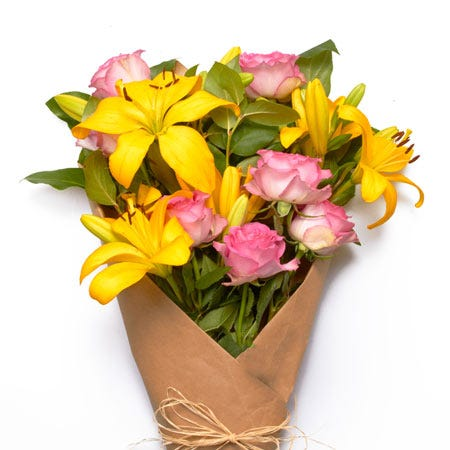 Wrapped yellow lilies and hot pink rose bouquet