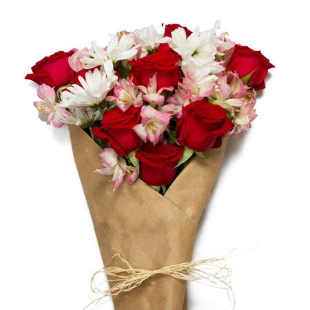 Wrapped flower bouquet with love flowers, red roses and pink alstroemeria