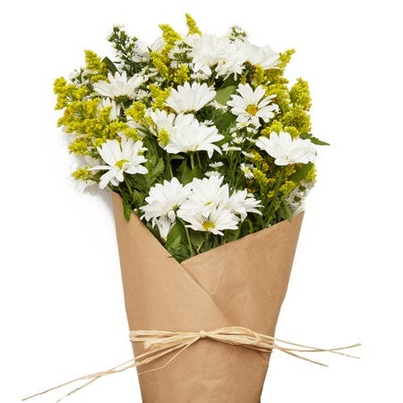 Paper wrapped flower bouquet with white daisies and yellow solidago