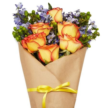 Paper wrapped rustic orange rose bouquet with berry for same day flower delivery