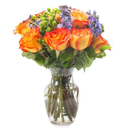 Orange roses, blue delphinium, green berries and a vase