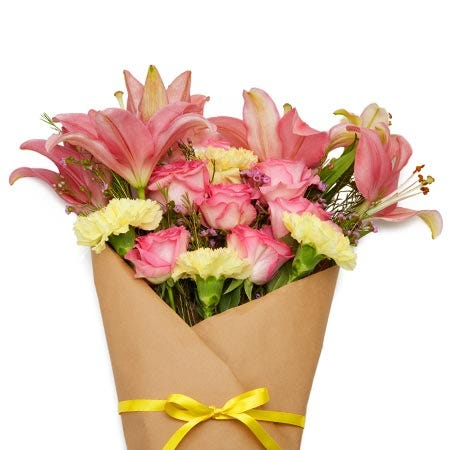 Pink rose and lily wrapped parchment paper wrapped flower bouquet delivery