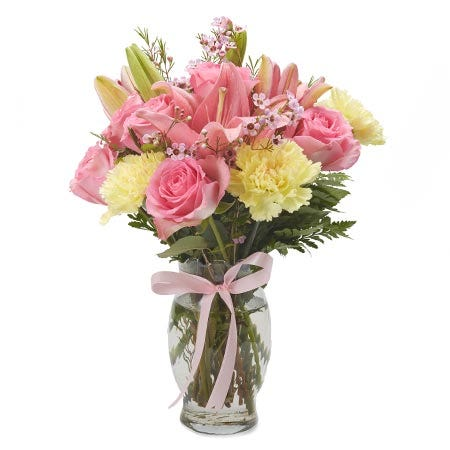 Yellow carnations, light pink roses and yellow carnations in a vase