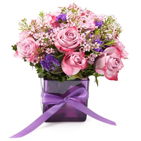 Purple bicolor rose bouquet with violets a lavender flowers in purple vase