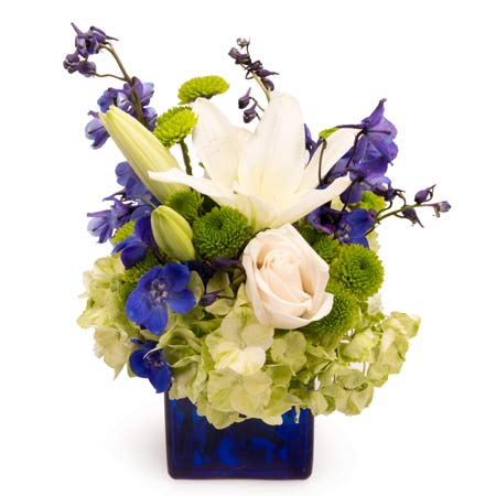 Green hydrangea bouquet with white lily flowers in a vase that's blue