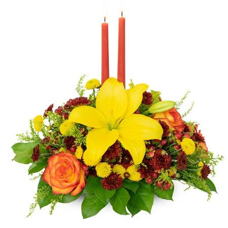 Yellow lily flower and candle centerpiece with two orange candles