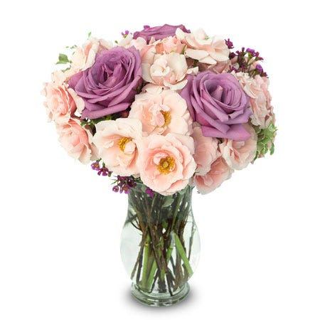 Purple roses and pink spray roses in a glass vase