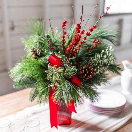 Mixed evergreen bouquet with red christmas flowers and red holiday berries