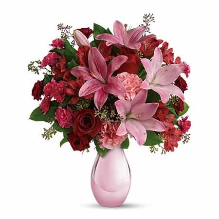 Pink lily, pink carnations, and red roses bouquet in a pink glass vase