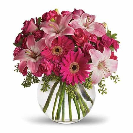 Adorable neon pink flower bouquet in round glass vase