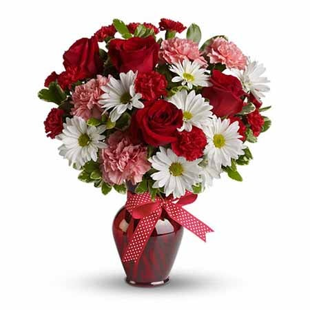Mixed bouquet with red roses, pale pink carnations, cheap flowers in a vase
