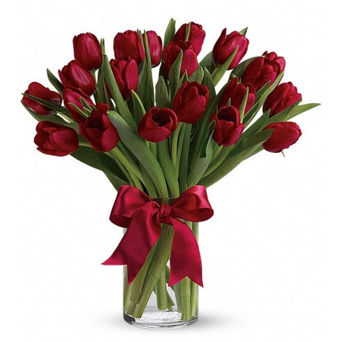 Red tulip bouquet with red tulips inside of a clear glass vase with red bow