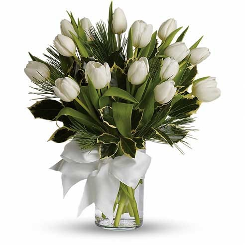 White tulip bouquet with white tulips inside of a clear glass vase with white bow