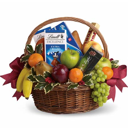 Chocolate and fruits gifts basket with chocolate bars, bananas, grapes and oranges