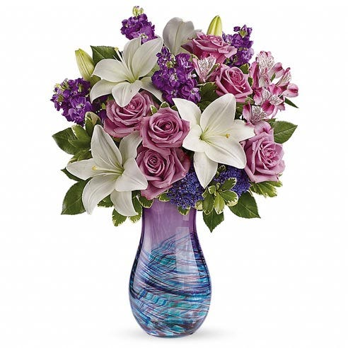 Luxury purple rose and white lily bouquet in a swirl purple and blue glass vase