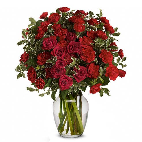 Miniature red roses and red carnations mixed flower bouquet in clear vase