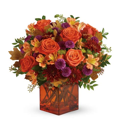 Orange roses, orange alstroemeria and purple mums in a square orange vase