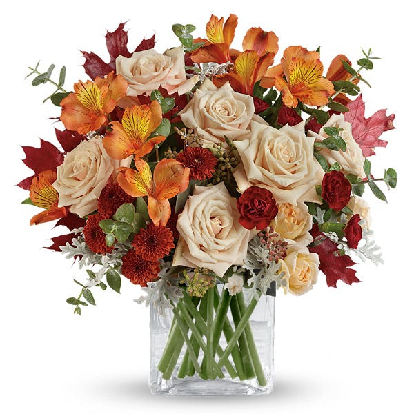 Fall peach roses bouquet in a wooden leaf print square vase with orange alsroemeria