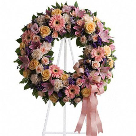 Pastel circle flower wreath standing funeral spray delivery at Send Flowers