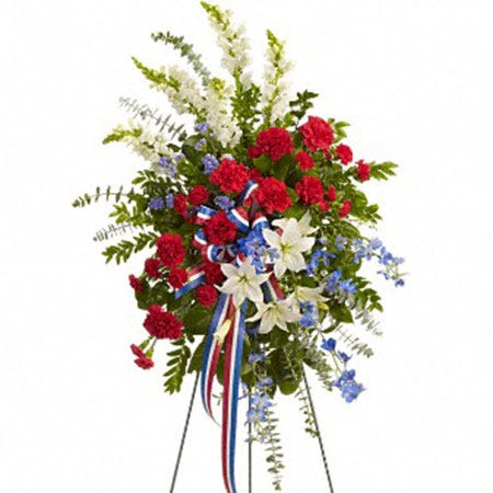 Oval shaped red carnation and white lily funeral flowers standing spray