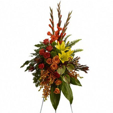 Orange orchid, orange rose, and red gladioli oval funeral flowers standing spray