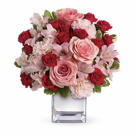 Pink roses, red spray roses and pink alstroemeria in a square vase