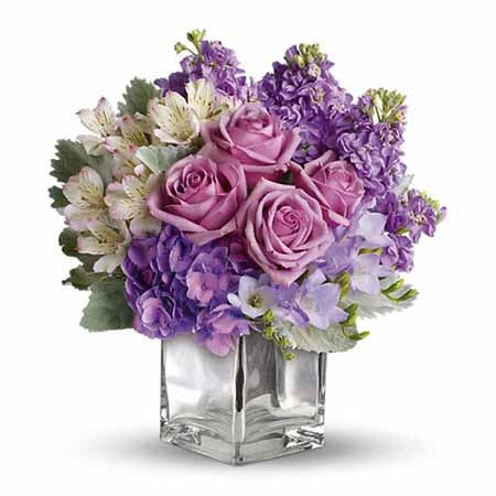 Southern flower bouquet with purple roses and purple flowers in a glass vase