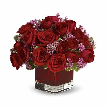 Romantic red roses and purple waxflower bouquet in a square dark red glass vase