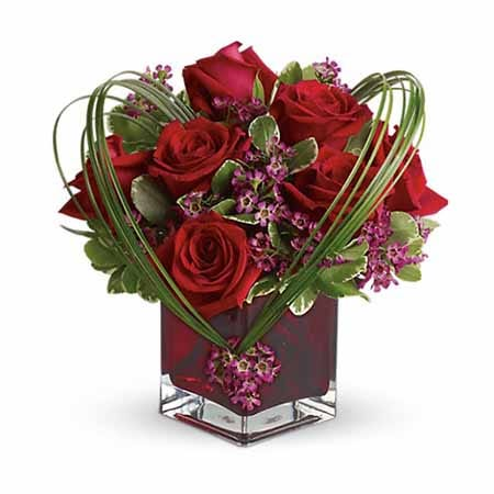 Modern heart shaped red roses and purple waxflower bouquet in red square vase