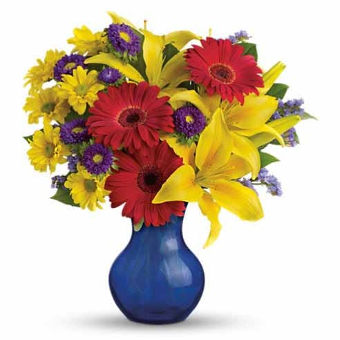 Red gerbera daisy and yellow asiatic lilies bouquet in a dark blue vase