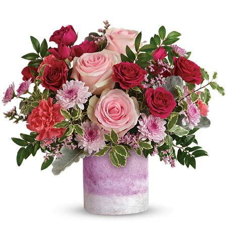 Pale pink roses, red roses, pink chrysanthemums and peach carnations in a pink vase