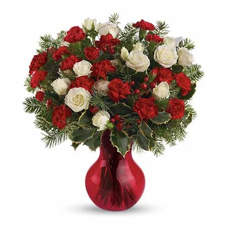 White spray roses and red mini carnations with holly in a red vase
